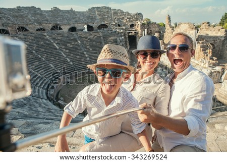 Young positive family take a vacation photo on the Side amphitheater  view - stock photo