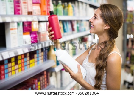 Young positive girl buying shampoo in shopping mall - stock photo