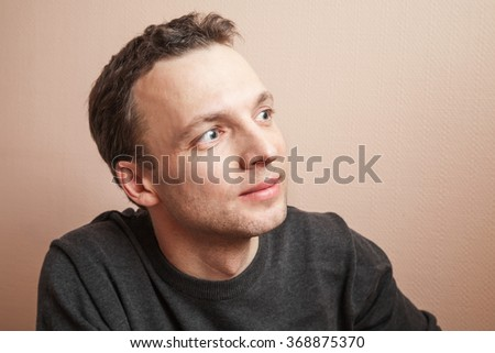 Young positive handsome Caucasian man studio portrait over gray wall background - stock photo