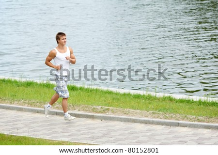 Young positive man jogging in park outdoors - stock photo