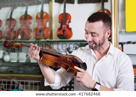 Young positive man with beard purchasing traditional violins in store
