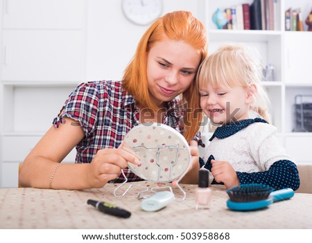 Young positive mother looking at mirror with small daughter indoors