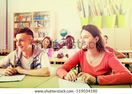 Young positive multiethnic students studying together in the classroom