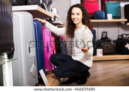 Young positive woman choosing travel suitcase in haberdashery shop