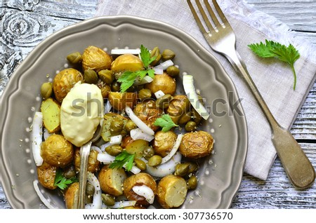 Young potato salad with capers and marinated onion on rustic background. - stock photo