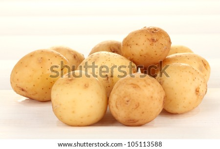 young potatoes on white wooden table close-up
