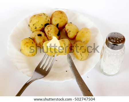 Young potatoes with butter and salt on white dish close up.