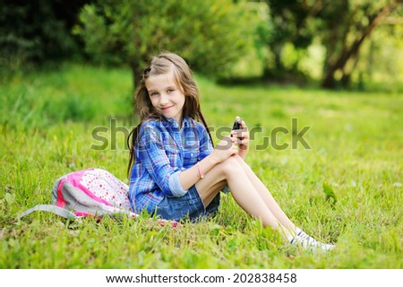 Young pre-teen girl with long brunette hair texting while hanging out on the green lawn  - stock photo