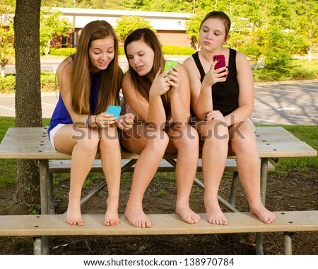 Young pre-teen girls texting while hanging out in front of their school - stock photo