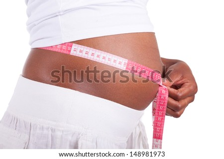 Young pregnant black woman measuring her belly, isolated on white background - African people