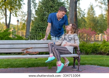 Young pregnant couple - at the autumn park smiling at the bench