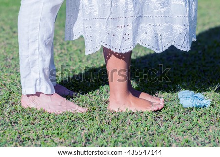 Young Pregnant Couple Feet With Newborn Baby Booties In Nature  - stock photo