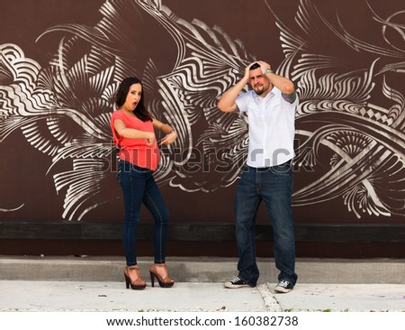 Young pregnant couple in a playful pose. - stock photo