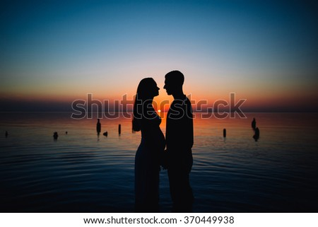 Young pregnant couple in love on summer sunny evening. at sunset on the beach - stock photo