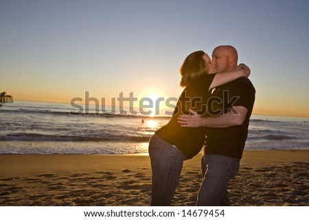 Young Pregnant Couple on the Beach at Sunset - stock photo