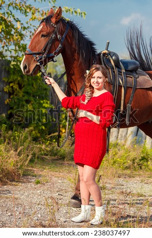 Young Pregnant couple riding a brown horse at countryside at summer