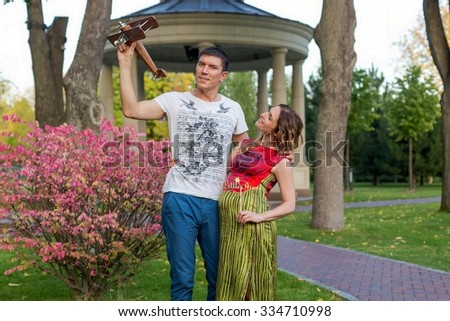 Young pregnant couple - with toy airplane outdoor
