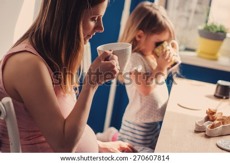 young pregnant mother drinking tea for breakfast with her toddler daughter at home - stock photo