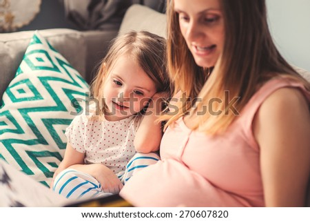 young pregnant mother reading book to her toddler daughter at home - stock photo
