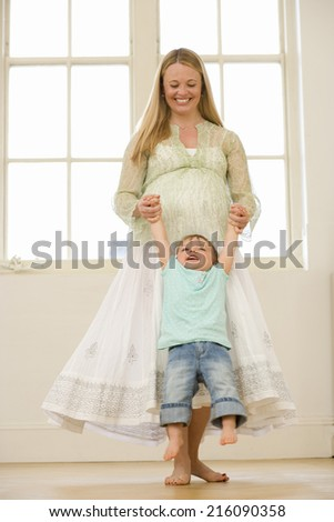 Young pregnant mother swinging toddler son (15-18 months), smiling, low angle view - stock photo
