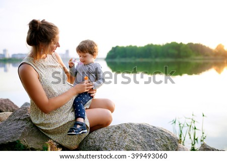Young pregnant mother walking with her little son in summer near the lake