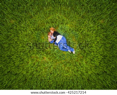 Young pregnant mother with her son lying and talking together in green wheat field. Aerial view of people. Family using drone for selfie taking.