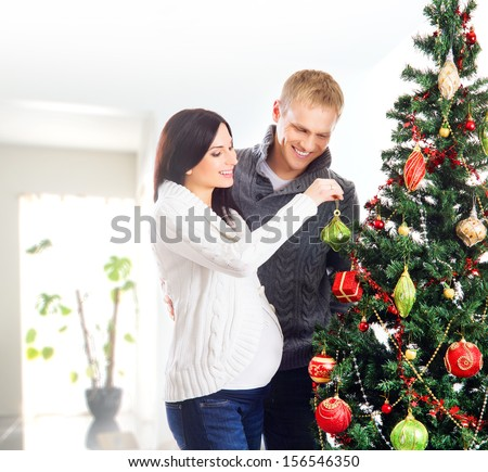 Young pregnant woman and happy father decorating Christmas tree  - stock photo