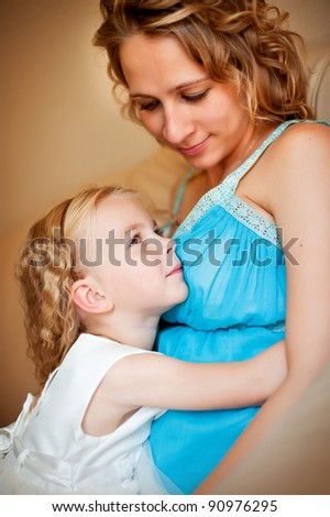 Young pregnant woman and her beautiful daughter sitting and holding mother's belly
