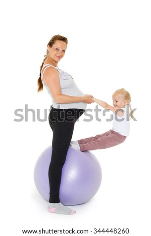 Young pregnant woman and small daughter with fitness ball on a white background. Healthy family. - stock photo
