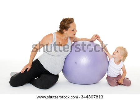 Young pregnant woman and small daughter with fitness ball on a white background. Healthy family.