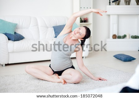 Young pregnant woman do yoga indoors - stock photo