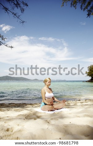 young pregnant woman does yoga on a beach in Thailand