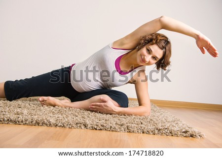 Young pregnant woman doing yoga exercises at home - stock photo