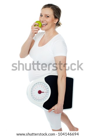 Young pregnant woman enjoy fresh green apple and holding weighing scale in other hand hand - stock photo