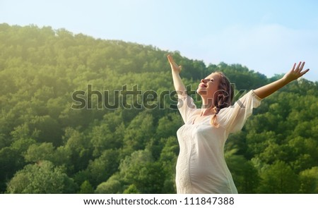 young pregnant woman enjoying life outdoors in summer - stock photo