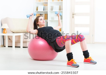Young pregnant woman exercising with dumbbells and gym ball at home