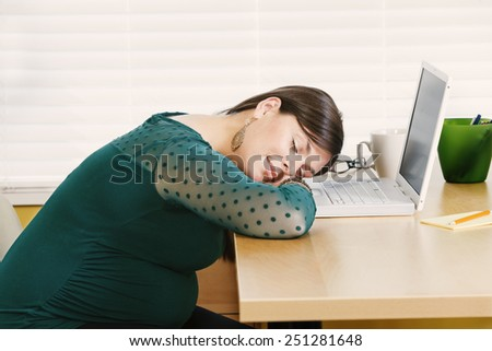 Young pregnant woman having a nap at her desk. - stock photo