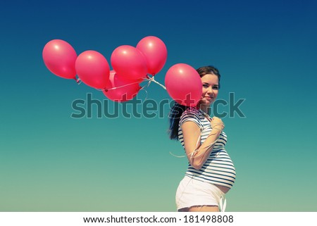 young pregnant woman holding red balloons - stock photo