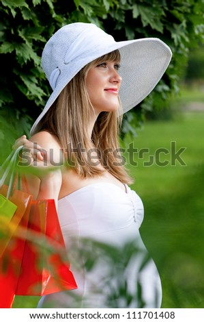 Young pregnant woman holding shopping bags - outdoors - stock photo