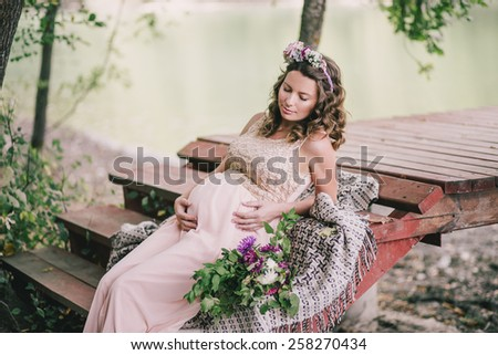 Young pregnant woman in a pink dress sitting on berth near lake - stock photo