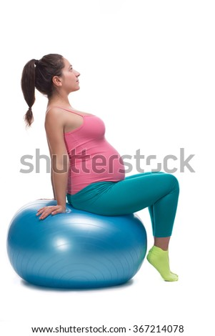 Young pregnant woman in bright sportswear sitting on the big blue ball for fitness - stock photo