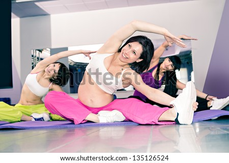 young pregnant woman in sport dress at an aerobic exercise - stock photo
