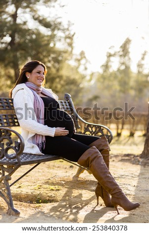 Young pregnant woman in the autumn park - stock photo