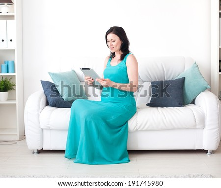 Young pregnant woman in the bedroom with tablet - stock photo