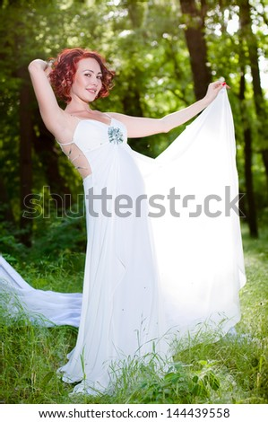 young pregnant woman in white dress in the garden