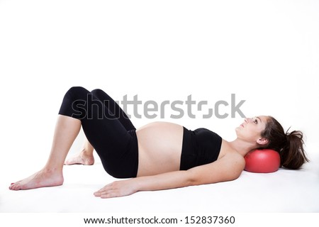Young pregnant woman is relaxing using overball - stock photo