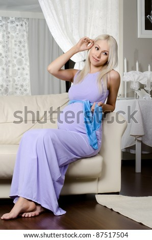 young pregnant woman lie  on white sofa in light  home room - stock photo