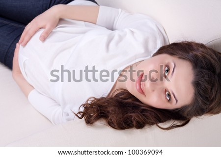 Young pregnant woman lying on sofa