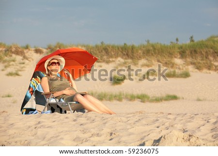 Young, pregnant woman, lying on the beach, relaxing and enjoying the sun. - stock photo