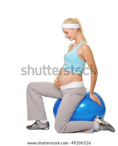 Young pregnant woman making exercise on a fitness ball - stock photo